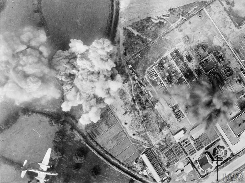 ROYAL AIR FORCE: FIGHTER COMMAND, TACTICAL AIR FORCE, 1943. (C 3770) Vertical aerial photograph taken during an daylight attack on the transformer station at Mur de Bretagne near Lake Guerledan, Brittany, by 12 Douglas Bostons of No. 342 (Free French) Squadron RAF. A Boston flys over the target as a direct hit is made on the the south end of the busbars and isolating switches adjoining the transformer control house (right), and also close to a pylon carrying overhe...